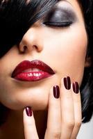 ansikte av kvinna med vackra mörka naglar och röda läppar foto