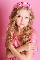vacker ung flicka på rosa bakgrund foto
