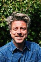 man med femtiotalet blont hår framför grönt bladverk. foto