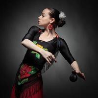 ung kvinna som dansar flamenco med kastanjetter på svart