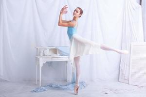 professionell balettdansös som poserar på vitt