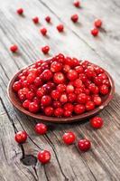 färska röda bär på träbord foto