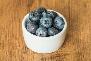 blåbär i en skål på ett träbord foto