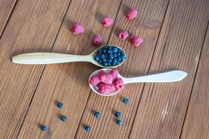 hallon och blåbär i skedar på träbakgrund. äta nyttigt foto