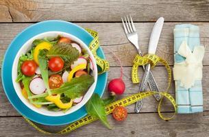färsk hälsosam sallad och måttband. hälsosam mat foto