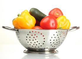 färska grönsaker i silver durkslag isolerad på vit foto