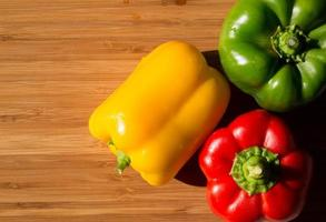 färsk paprika på träbord foto