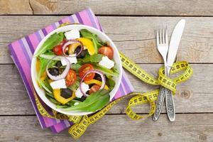 färsk hälsosam sallad, bestick och måttband foto
