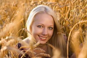 vacker blond kvinna som ler vid vetefältcloseupen foto