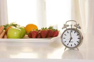 väckarklocka med bricka med färsk frukt på morgonen foto