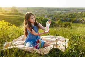 flicka i gräs med vattenflaska av plast foto