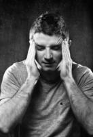 man lider av migrän och huvudvärk sjuk med händerna i tempo foto