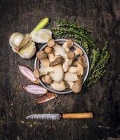 rå svamp med timjan, färsk vitlök, lök och vintagekniv foto