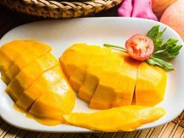 skiva mango på vit maträtt. foto