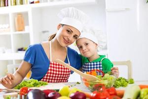 härlig mamma och unge två kockar i köket foto