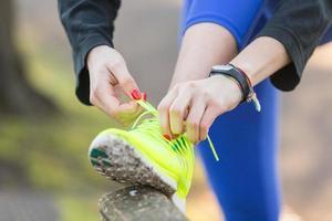 ung sportig kvinna som gör upp sina skor innan hon kör. foto