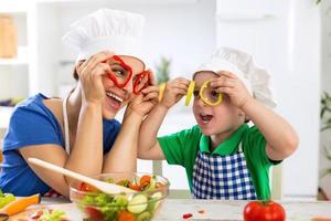 lycklig familj som leker med grönsaker i köket foto