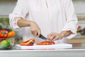 närbild på kvinna som skär färska grönsaker foto