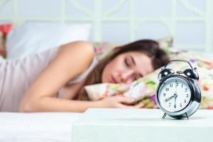 den unga flickan som sover i sängen foto