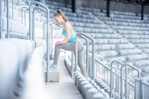 kvinnlig fitness tränare förbereder sig för träning, stretching och gör squats foto