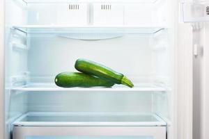 två gröna zucchini på hyllan med öppet tomt kylskåp foto