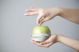 grönt äpple i kvinnliga händer på grå bakgrund foto