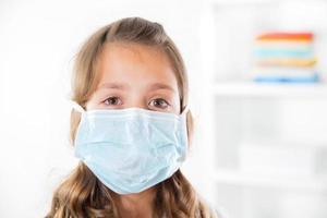 liten flicka som bär en skyddande mask foto