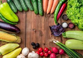 de mångfärgade grönsakerna på träbord foto