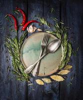 sked och gaffel på tallrik med örter kryddor ram