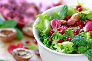 lockigt endivsallad med granatäpple, nötter, rosenblad ... foto