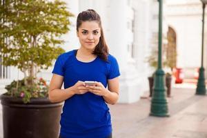 söt flicka smsar på en telefon foto