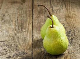två färska gröna päron med droppar vatten på bordet foto