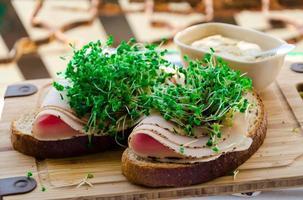 bröd med rökt kalkonskinka, broccoli groddar och senap foto