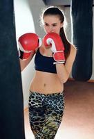 vacker flicka idrottare tränar på en boxning gym foto