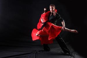 manlig dansare i svart håller upp kvinnlig dansare i rött
