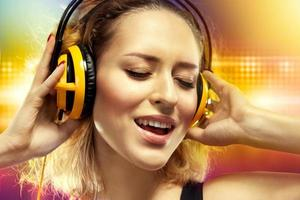 glad kvinna lyssnar musik med hörlurar