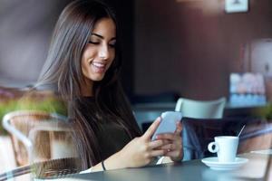 vacker flicka som använder sin mobiltelefon i café. foto