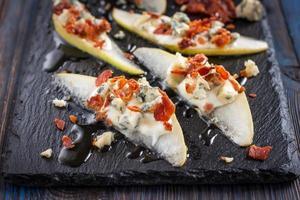 päron med gorgonzola, bacon och honung på svart bakgrund foto