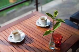 två moderna espressokoppar på ett träbord