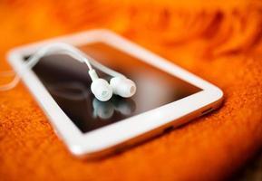 vita hörlurar och surfplatta, närbildfoto, liten dof foto