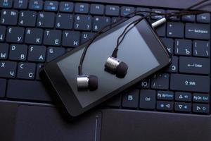 hörlurar och mobiltelefon vid tangentbordet. foto
