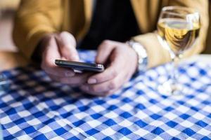 man använder en mobiltelefon i restaurang, café, bar