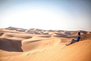 flicka sitter på kanten av öknen dyn foto