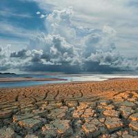 regnar moln över klimat som spricker mark foto