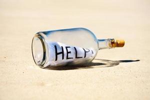 hjälp! meddelande i en flaska på öde strand foto