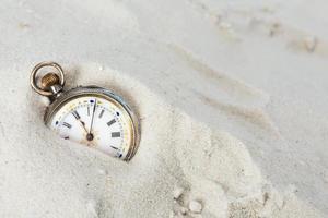 gammal klocka i sanden foto