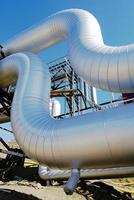 industriområde, stålrörledningar och ventiler mot blå himmel foto