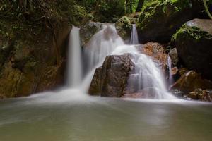 vattenfall i djup skog foto