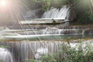 vackert vattenfall med solstråle skogen foto