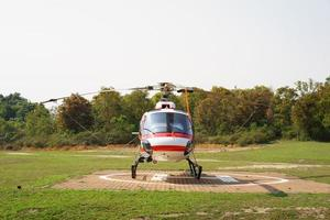 helikopter parkerad vid helikopterplattan nära skogen. foto